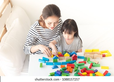 asian baby and her mother play puzzle wood toy, leaning and development