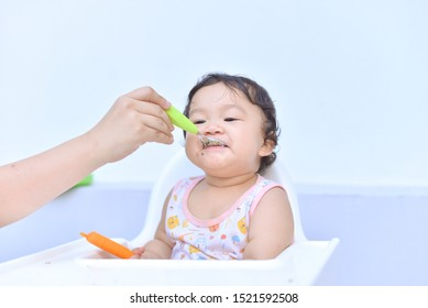 Asian baby kid enjoy eating with happy on white background