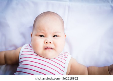 Asian baby lie supine on white background