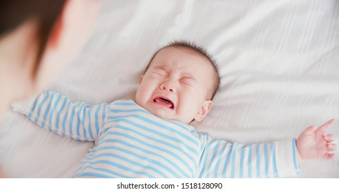 asian baby lying on the bed and crying