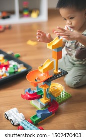 Asian baby playing the marble run blocks in the living room.