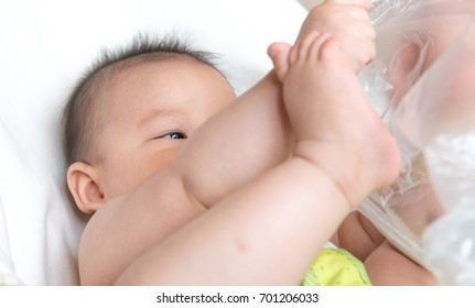 An Asian baby is playing on a bed surrounded by pillows.Baby is naked with diaper.