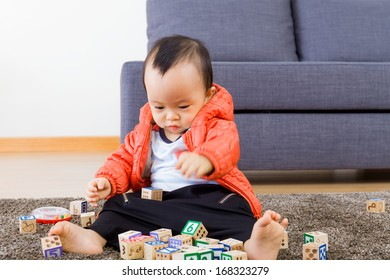 Asian baby playing wooden block at home