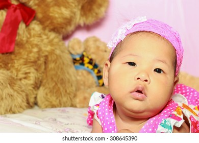 Asian baby poses on pink background and have teddy bear is friends.