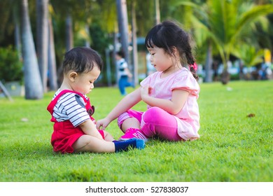 Asian baby sibling boy and girl play in the park