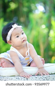 Asian baby sitting in the garden