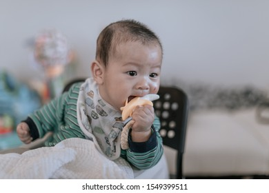 Asian baby sitting on chair playing theeting banana toy with scratched and wounded face from his hand at home