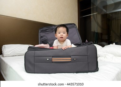 Asian baby sitting in travel suitcase placed on hotel double bed