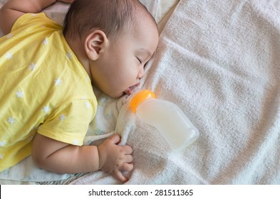 Asian baby sleeping and drinking milk