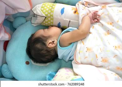 Asian baby sleeps in the crib
