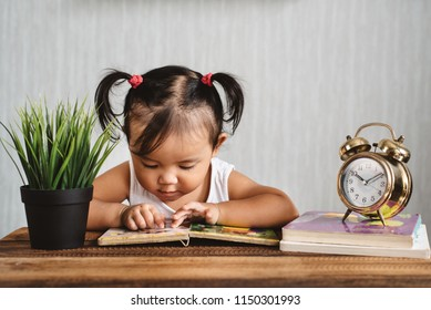asian baby toddler reading book on wooden table with alarm clock. concept of early education, child learning and development