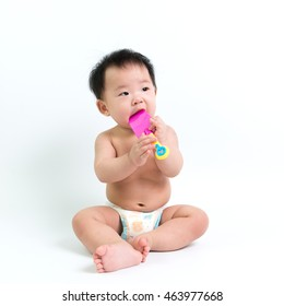 Asian baby wearing diaper sitting up on white background