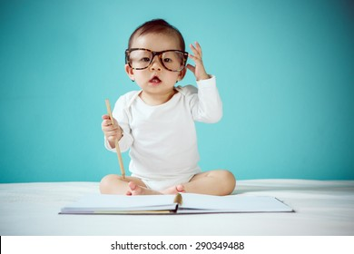 Asian baby writing in a book and sitting on the bed in the blue bedroom, Baby healthy and preschool concept