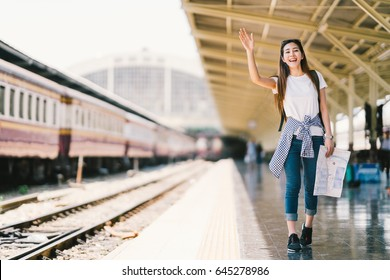 Asian backpack traveler woman holding generic local map and waving hand at train station platform, summer holiday travelling or young tourist concept