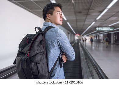 Asian backpacker walking on travelator in the international airport, International airport tourist passenger with backpack at airport on holiday, Vacation time