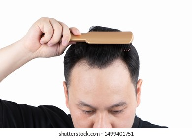 Asian bald man alopecia hand holding comb on bald head isolated on white background. Human hair loss solution and hair transplant concept.