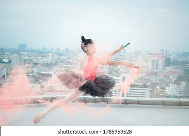 Asian ballerina dancer girl practicing ballet dancing with colored smoke bomb on rooftop with skyscraper city view, adorable child dancing in ballet