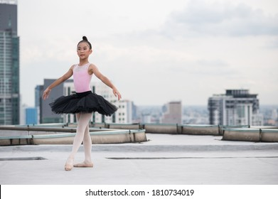 Asian ballerina girl dancing on the rooftop of the building city background.