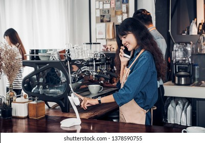 Asian Barista use tablet take order from customer in coffee shop,cafe owner writing drink order at counter bar,Food and drink business concept,Service mind concept.restaurant waiter worker.