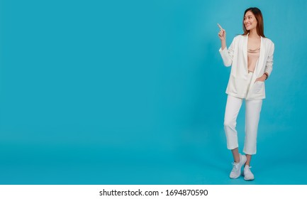 Asian beautiful business women blogger are posture hand pointing.Full length standing isolated on blue color background with copy space.Concept of online shopping business with Promotion and Sale.