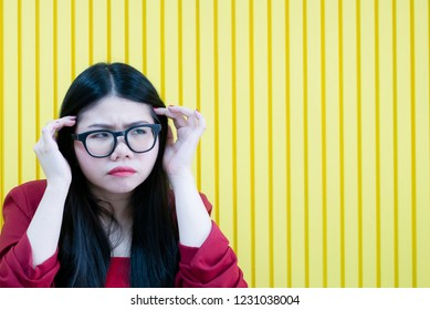 Asian beautiful business women in casual red suit with glasses having skeptical and dissatisfied look expressing Distrust,skepticism and doubt isolated over yellow background,suspicious skepticism,