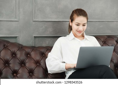Asian beautiful businesswoman,wore white shirt Sitting on brown sofa in the living room Working with notebook computers
