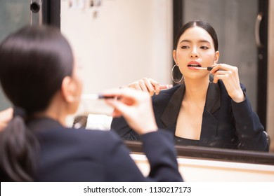 Asian beautiful and elegant girl wearing luxurious black suit putting on lipgloss cosmetics on lips