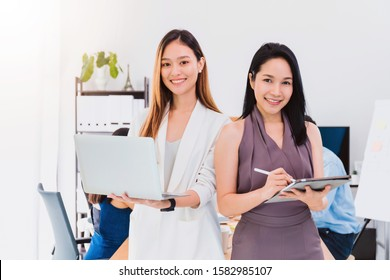 Asian beautiful empower woman holding laptop and and tablet with friend working at meeting room in office.Owner businesswoman startup with confident and cheerful.