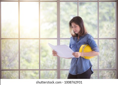 Asian beautiful female engineer in blue jeans shirt standing and read plan in paper, holding yellow safety helmet with glass frame in background
