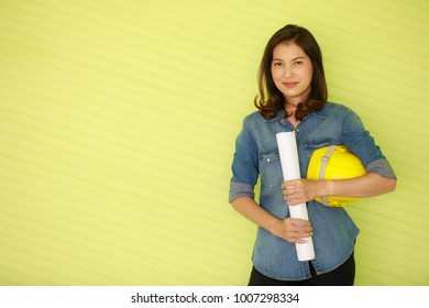 Asian beautiful female engineer carrying white paper roll and holding yellow safety helmet, standing in front of colorful green background