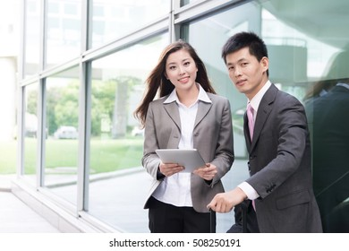 asian beautiful girl and businessman with tablet in modern hall