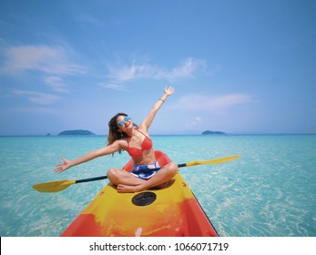 Asian beautiful girl enjoy with kayaking on the Andaman sea blue ocean and blue sky in summer time with holiday vacation in summer season concept