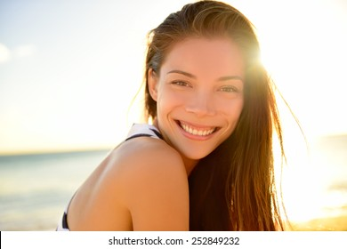 Asian beautiful girl smiling happy on beach vacation enjoying warm sunshine. Mixed race Asian Caucasian pretty model outside with sun in background on Hawaiian tropical beach.