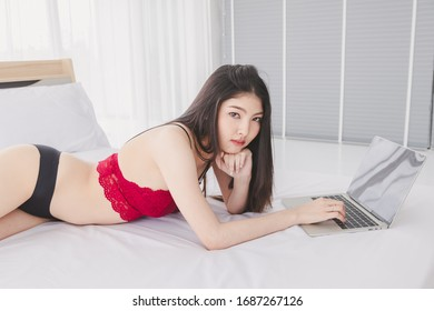 Asian beautiful girl wearing casual clothes and play or work with computer. Happily in the house. Concept Work for home and relax time.