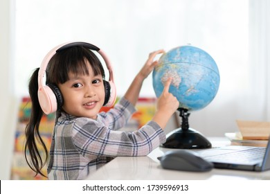 Asian beautiful little student girl is smiling and pointing on bilingual globe model for her online lesson, concept of learn from home and homeschooling for child education in the outbreak of covid 19