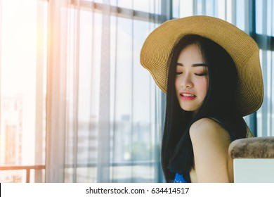 Asian beautiful long black hair woman with a hat fashion posing indoors in warm glow of the sun. Portrait of girl relaxing, thinking in the living room. Travel and lifestyle concept.