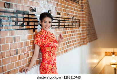 Asian beautiful model girl wearing gipao dress or red cheongsam. Happy Chinese New Year festival.