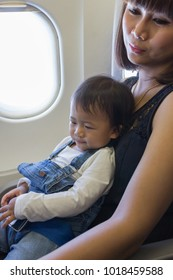 Asian beautiful mother and cute baby is sitting in fight airplane.