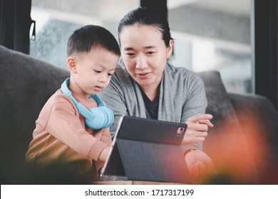 Asian beautiful mother Watching his 3-year-old son learn via online technology using a tablet.Home learning concepts During school holidays.