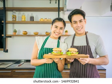 Asian beautiful smile woman 24 years old and Asian Handsome smile man 24 years old stand hold two delicious the hamburger on a wooden tray.That they helped to do to sell Both of them looked forward