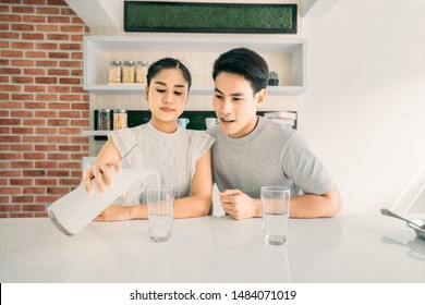 Asian beautiful smile woman 24 years old, sitting Pour milk into two glass on the table beside with Asian Handsome smile man 24 years old  Both of them looked forward in the morning. back to school