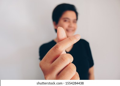 Asian beautiful smiling girl with short hair and showing love korea sign with finger with blurred background isolated white background. Indonesian Women