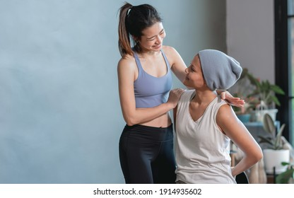 Asian beautiful sportive trainer is coaching a cancer patient to do exercise and yoga at home. Sport and Health Concept.