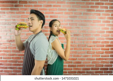 Asian beautiful woman 24 years old and Asian Handsome man 24 years old stand eating two delicious the hamburger Two people collide with each other. Both of them looked forward