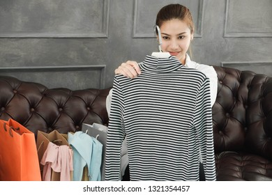 Asian beautiful woman Is admiring the newly purchased clothes She's shopping online on the internet.