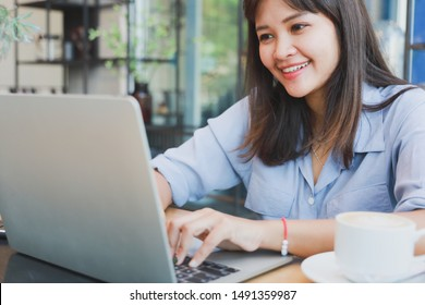 Asian beautiful woman  in blue shirt  using laptop and drinking coffee in coffee shop cafe happy and smile face