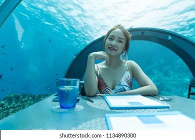 Asian beautiful woman dinner on undersea world background,  underwater restaurants in Maldives.