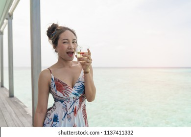 Asian beautiful woman enjoyful drink cocktail in resort island, vacation holiday concepts with tropical Maldives island background.