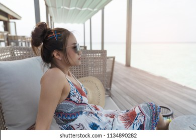 Asian beautiful woman enjoyful on sofa, vacation holiday concepts with tropical Maldives island background.