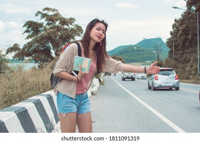 An asian beautiful woman get lost and hitchhiking beside street while traveling in summer time.